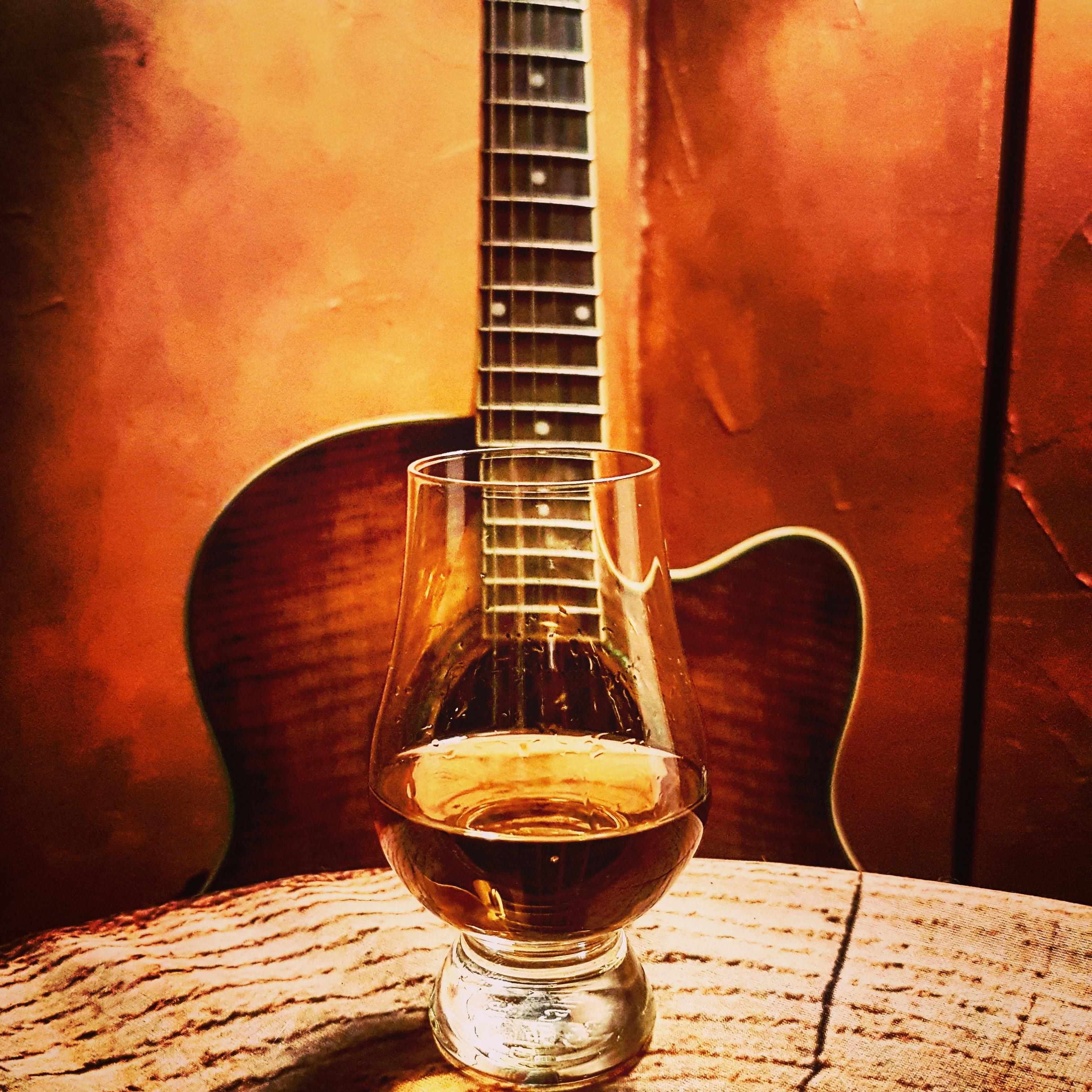Ein Glas Whisky mit einer Gitarre im Hintergrund.