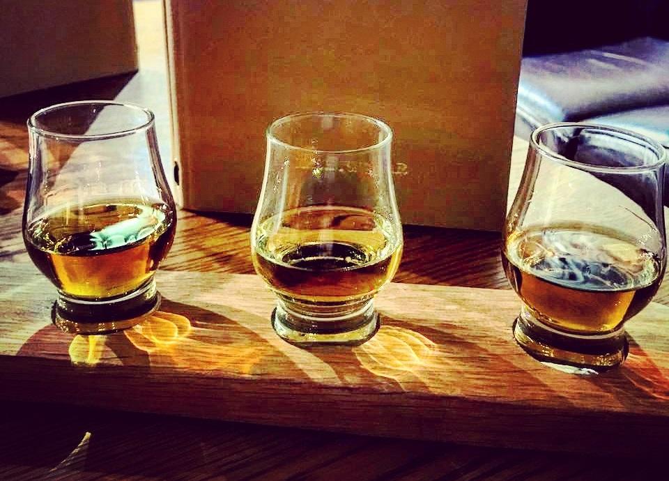 Whisky Tasting aus drei Drams präsentiert auf einem Holzbrett